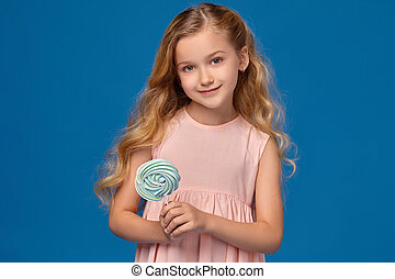 Fashionable little girl in a pink dress, with a candy in her hands, standing on a blue background.