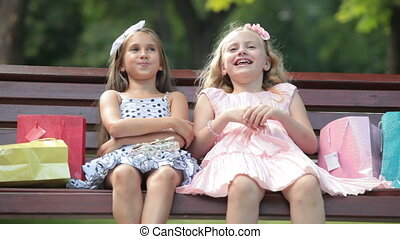 Fashionable little girls conversation on a bench in the...