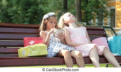 Fashionable little girls in summer dresses on a bench
