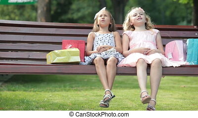 Fashionable little girls with shopping bags relaxing on the bench