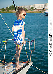 fashionable little kid aboard luxury boat in summer sea cruise