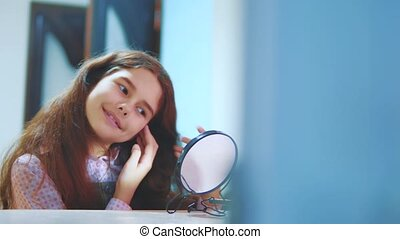Fashionable little lady combing her hair and looking in the...