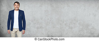 fashionable man is smiling standing over grey studio wall
