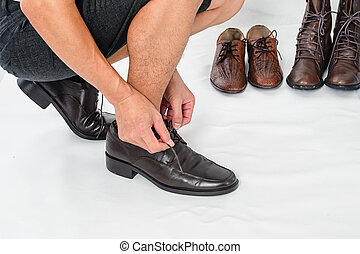 Fashionable Men's Classic Leather Shoes ,man ties up his shoelaces on white background
