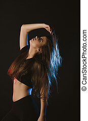 Fashionable model with long brunette hair posing at studio