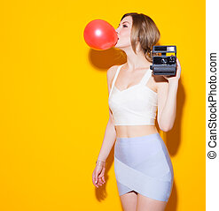 Fashionable modern girl posing in colorful top and skirt inflates the red bubble from chewing gum and with a vintage camera in her hand on yellow background in the studio. Fashion Beauty Girl. Sexy Glamour Girl on Yellow background. Concept
