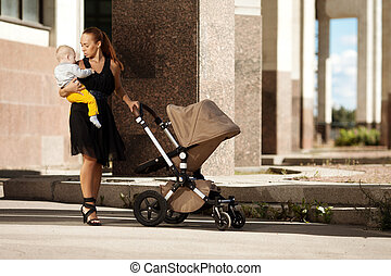 Fashionable modern mother on a city street with a pram....