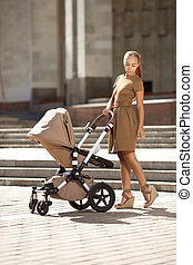Fashionable modern mother on a urban street with a pram....
