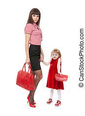 Fashionable Mom in red shoes and her little daughter with a beautiful handbag. Studio portrait, isolate on white.