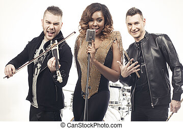 Fashionable music band posing. Two handsome man and beautiful sexy woman with music instruments