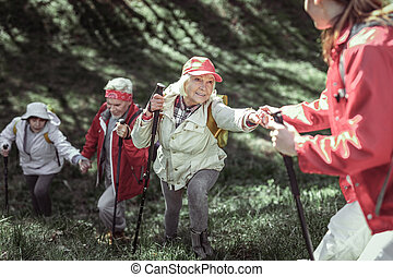 Fashionable old folk having Nordic walking in forest