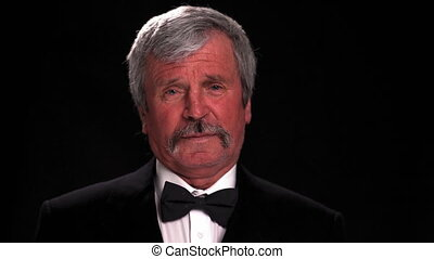 Fashionable old man in tuxedo happily looks at the camera in a dark room isolated on a black background. Prores 422