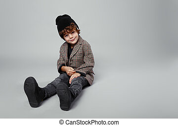 Fashionable portrait of a cute boy seated down in studio, wearing fashionable with black hat, looking adorable, isolated on a white background.