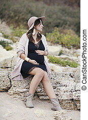 Fashionable pregnant woman in black dress outdoors