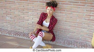 Fashionable sexy girl sitting on urban street