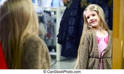 fashionable shop. little girl in a clothing store. chooses a suit
