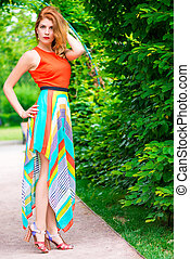 Fashionable slim woman in a bright dress outdoors