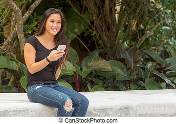 Fashionable smiling young pretty Asian woman texting on smart phone