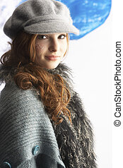 Fashionable Teenage Girl Wearing Cap And Knitwear In Studio