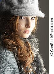 Fashionable Teenage Girl Wearing Cap And Knitwear In Studio