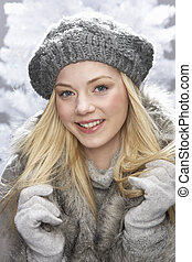 Fashionable Teenage Girl Wearing Cap And Fur Coat In Studio In Front Of Christmas Tree