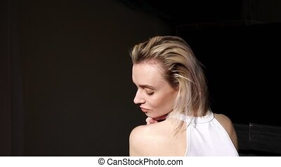 fashionable woman blonde poses with hair on black background...