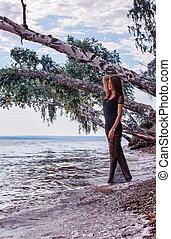 Fashionable woman by lake