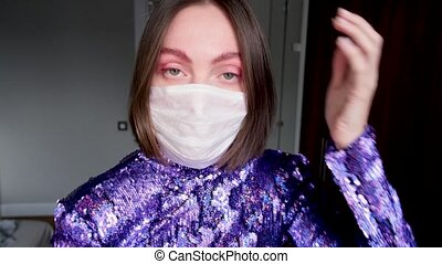 Fashionable woman going to quarantine party. Girl combing eyebrows, checking makeup and straightening her hair before leaving home during coronavirus quarantine