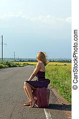 Fashionable woman hitchhiking at roadside - Fashionable...