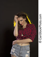 Fashionable woman in jeans shorts and plaid shirt