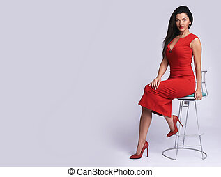fashionable woman in red dress sitting on chair.