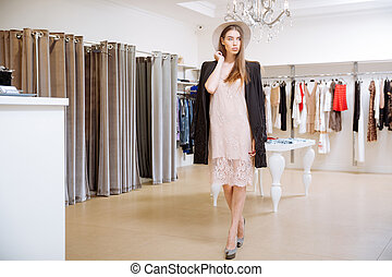 Fashionable woman standing in clothing shop