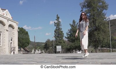 Fashionable woman tourist walking along a deserted