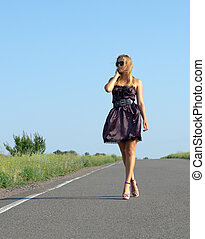 Fashionable woman walking on a country road