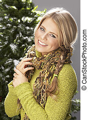 Fashionable Woman Wearing Knitwear And Scarf In Studio In Front Of Christmas Tree