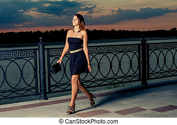 Fashionable women walking in evening time with her clutch in...