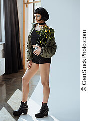 Fashionable young african american woman with potted plant in hand posing and looking away