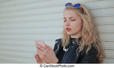 Fashionable young and beautiful girl with a smartphone in hands. The girl is looking at the phone screen. Against a background of white horizontal roller blinds.