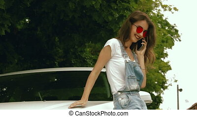 fashionable young brunette in glasses speaks on a mobile telephone near car