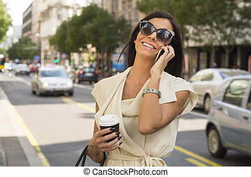 Fashionable young brunette laughs into phone