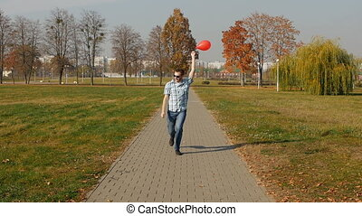 Fashionable young caucasian guy runs with a red balloon and...