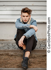 Fashionable young guy in stylish denim clothing and black shoes sits near a wooden wall