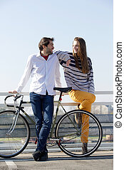 Fashionable young man and woman posing with bicycle outdoors