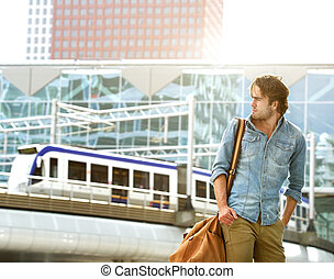 Fashionable young man traveling with bag