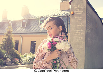 Fashionable young model in pink dress with flowers in hands on a background of city. Vintage toning effect