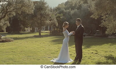 Fashionable young wedding couple enjoy each other in a park