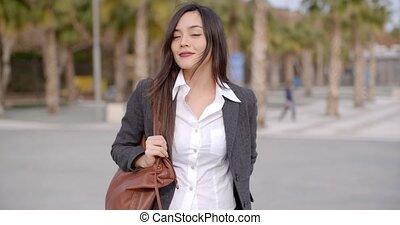 Fashionable young woman carrying a large handbag