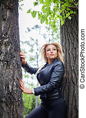 Fashionable young woman in leather jacket outdoors.