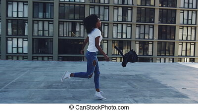 Fashionable young woman on urban rooftop running and ...