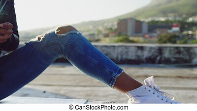 Fashionable young woman on urban rooftop using smartphone